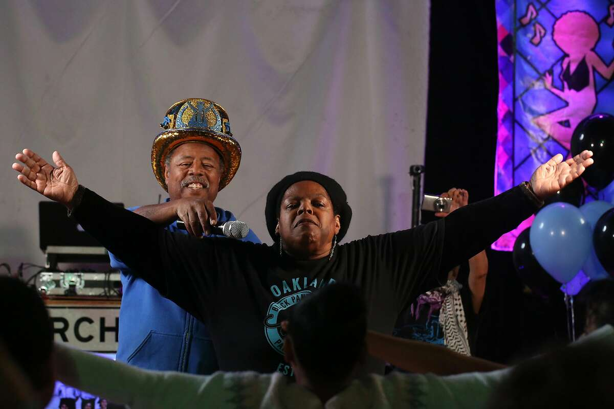 Katherine Campbell (right) leads children in some stretches as David Miles (left), owner Church of Eight Wheels, assists by holding a microphone before breakfast at the Black Panther Party's Free Breakfast for Children Program 50th year anniversary event she organized at the Church of Eight Wheels on Thursday, November 14, 2019 in San Francisco, Calif. Campbell started volunteering at the Back Panther Party's Free Breakfast for Children Program in 1969 which has inspired her in her work as a community specialist.