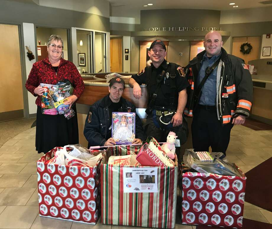 Above, a group presents donations to the Torrington Fire Department's annual Christmas for Children toy drive. Photo: /