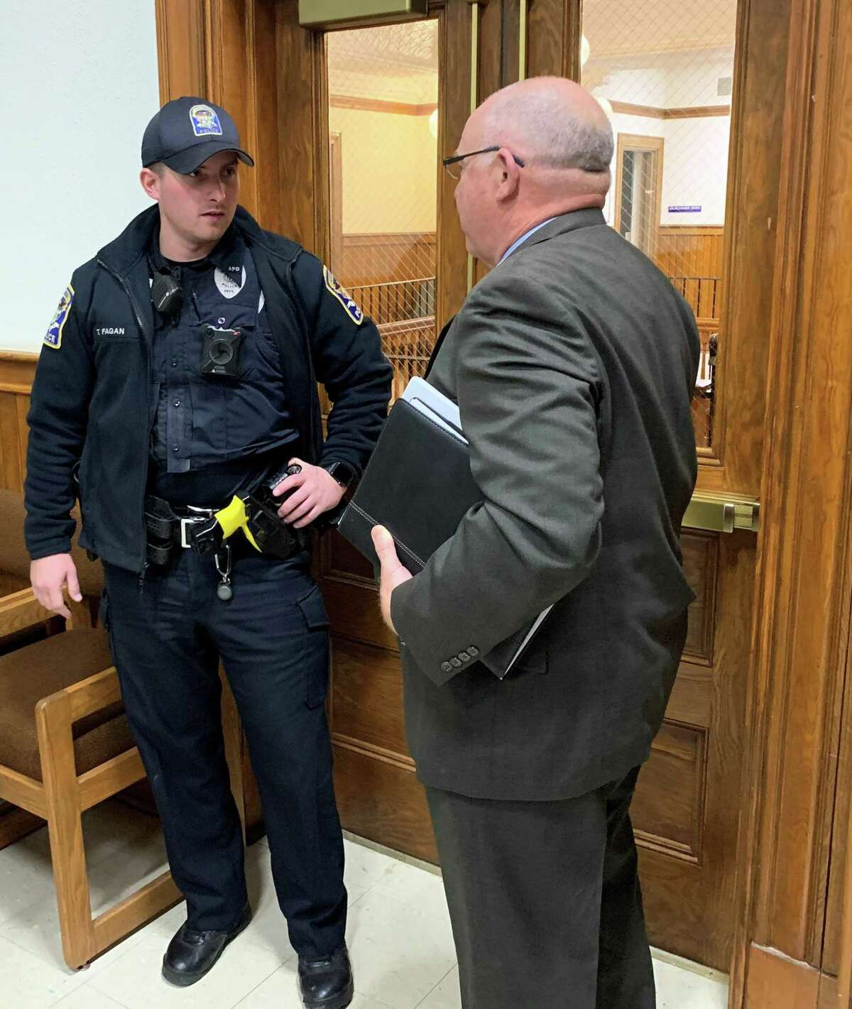 One of the two Ansonia police officers who responded to attorney Fred Dorsey's call to have Mayor David Cassetti removed talks to the school board lawyer. Dorsey declined time file a complaint because the mayor had left after adjourning the meeting.