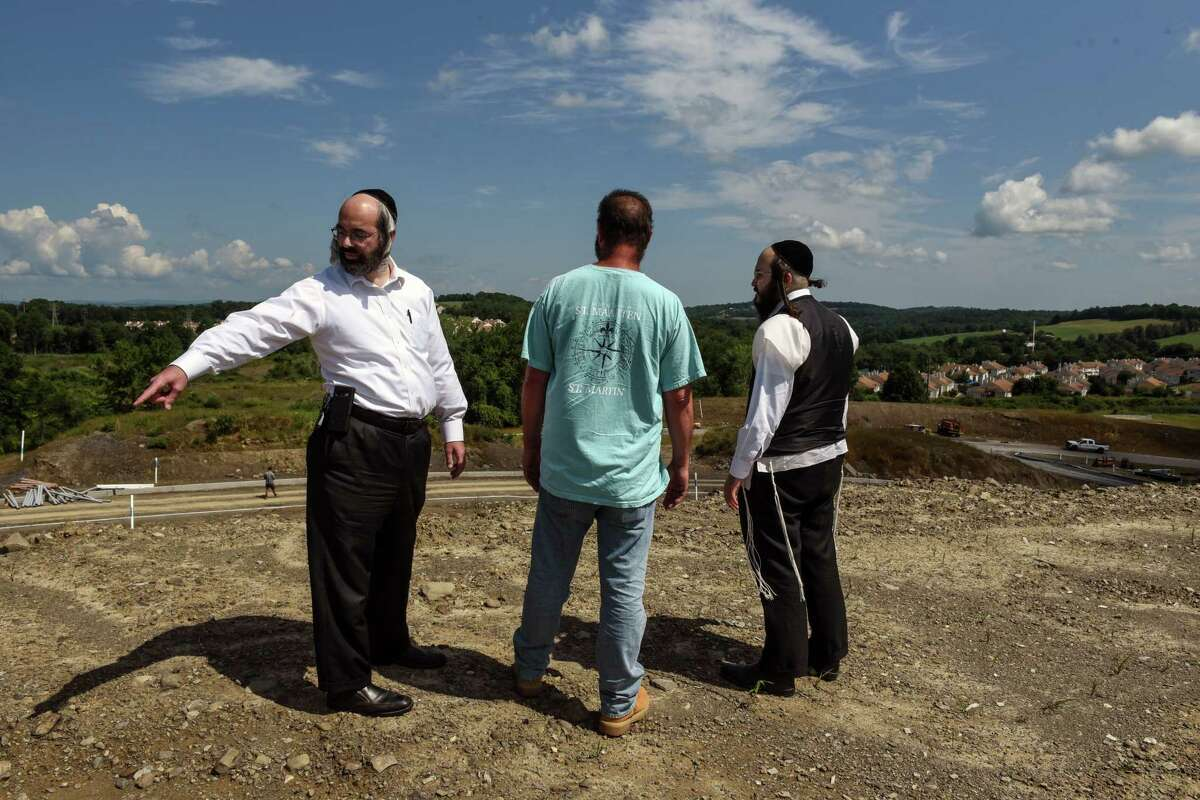 FILE -- Livy Schwartz, left, and Joseph Landau, right, with an engineer at the site of their proposed housing development in Chester, N.Y., on July 24, 2019. The developers have accused local officials of illegally blocking their project. (Stephanie Keith/The New York Times)