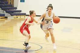Onekama's Sara Bromley drives into the lane against Benzie Central's Kylee Streeter.