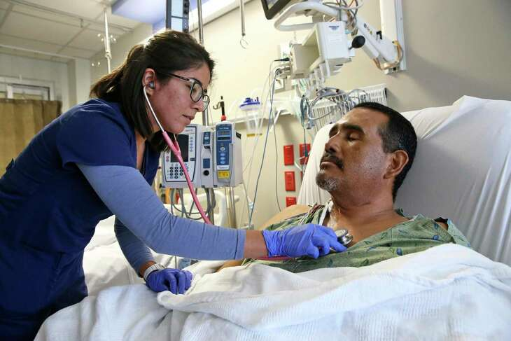 Ray Valdez, Jr. gets his vital signs checked by a nurse after a heart surgery at University Hospital.