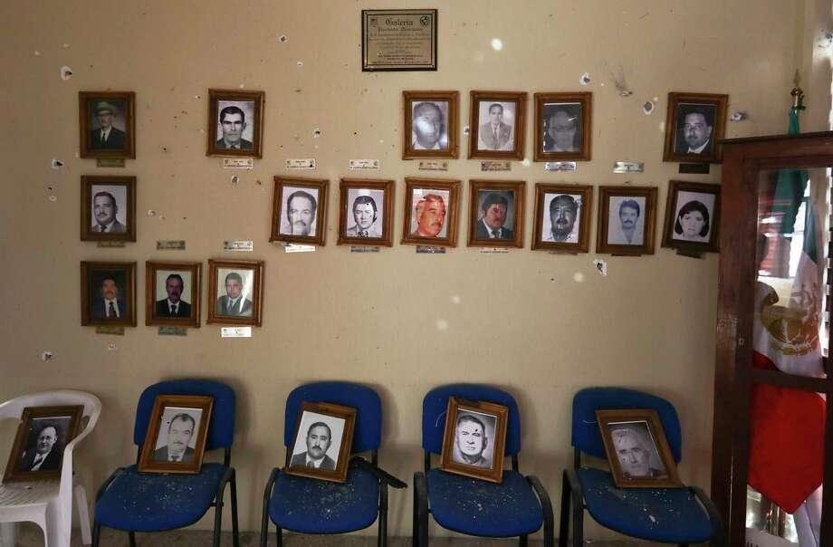 Retratos de ex presidentes municipales cuelgan en una pared del Ayuntamiento que fue perforada por las balas durante un tiroteo en Villa Unión, México, el 2 de diciembre de 2019. Photo: Eduardo Verdugo /Associated Press / Copyright 2019 The Associated Press. All rights reserved