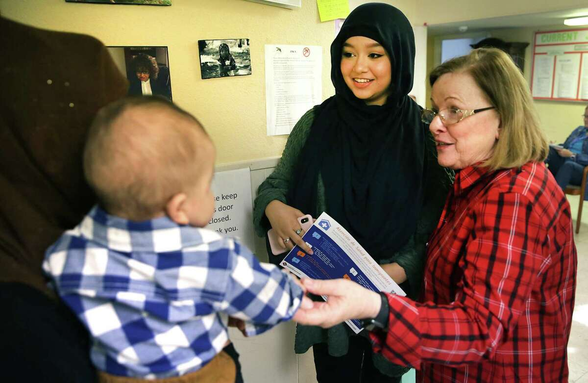 Hajar Bayat, center, a volunteer at the Center for Refugee Services helps interpret for a woman and her baby from Afghanistan, left, as Margaret Constantino, right, the center's director, listens.