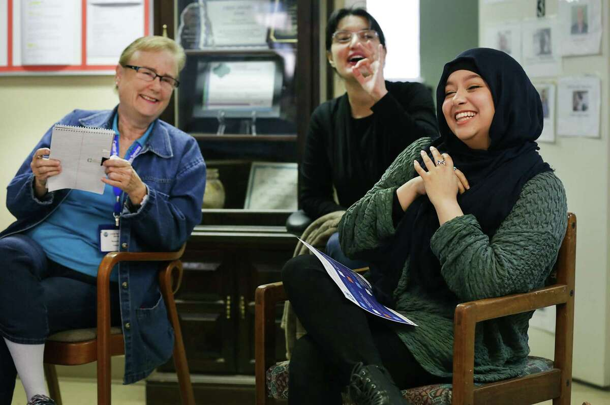 Manu Parker (left to right) employment coordinator for the center, Sabeen Abdullah and Hajar Bayat share a laugh at a staff meeting at the Center for Refugee Services on San Antonio's Northwest Side. Bayat moved from New Jersey to San Antonio with her family six years ago. She now volunteers at the center, helping new arrivals from the land of her parents' birth, Afghanistan. She was born in New Jersey.