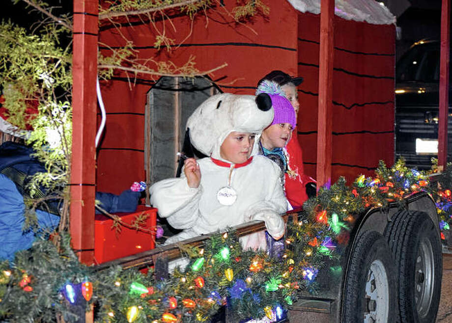 A child dressed as Snoopy throws candy Friday during the Christmas in Virginia parade. Photo: Samantha McDaniel-Ogletree | Journal-Courier