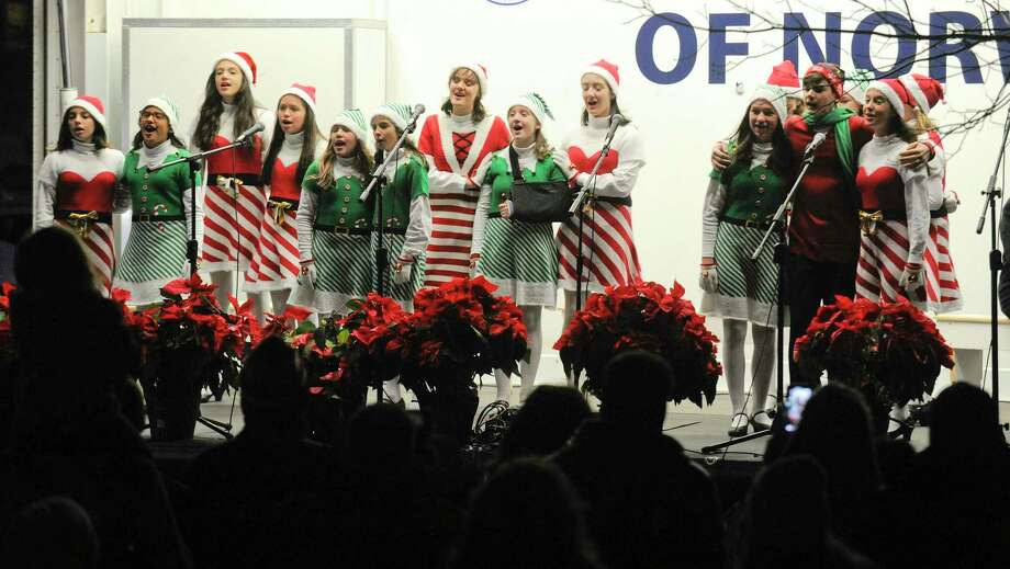 Above, members of the Crystal Theatre Performers sing Christmas Carols during the annual Holiday Tree Lighting Celebration on the front lawn of City Hall in Norwalk on Friday. Right, Photo: Matthew Brown / Hearst Connecticut Media / Stamford Advocate