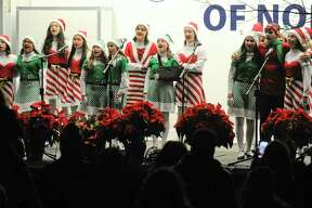 Above, members of the Crystal Theatre Performers sing Christmas Carols during the annual Holiday Tree Lighting Celebration on the front lawn of City Hall in Norwalk on Friday. Right,