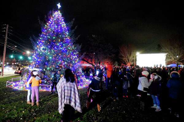 Residents snap photos infront of the Holiday Tree after it was lit on the front lawn of City Hall in Norwalk, Conn. on Dec. 6, 2019.