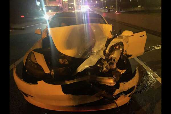 Photos from a collision on I-95 in Norwalk on Saturday, Dec. 7, in which a driver struck a police cruiser and a disabled vehicle with his Tesla, which he claimed was on auto-pilot, according to state police.