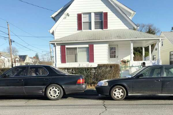"Two black sedans parked on Hobbie Street in the Cove section of Stamford share the same Connecticut license plate number. Capt. Richard Conklin said Stamford police see many instances involving ""split"" plates."