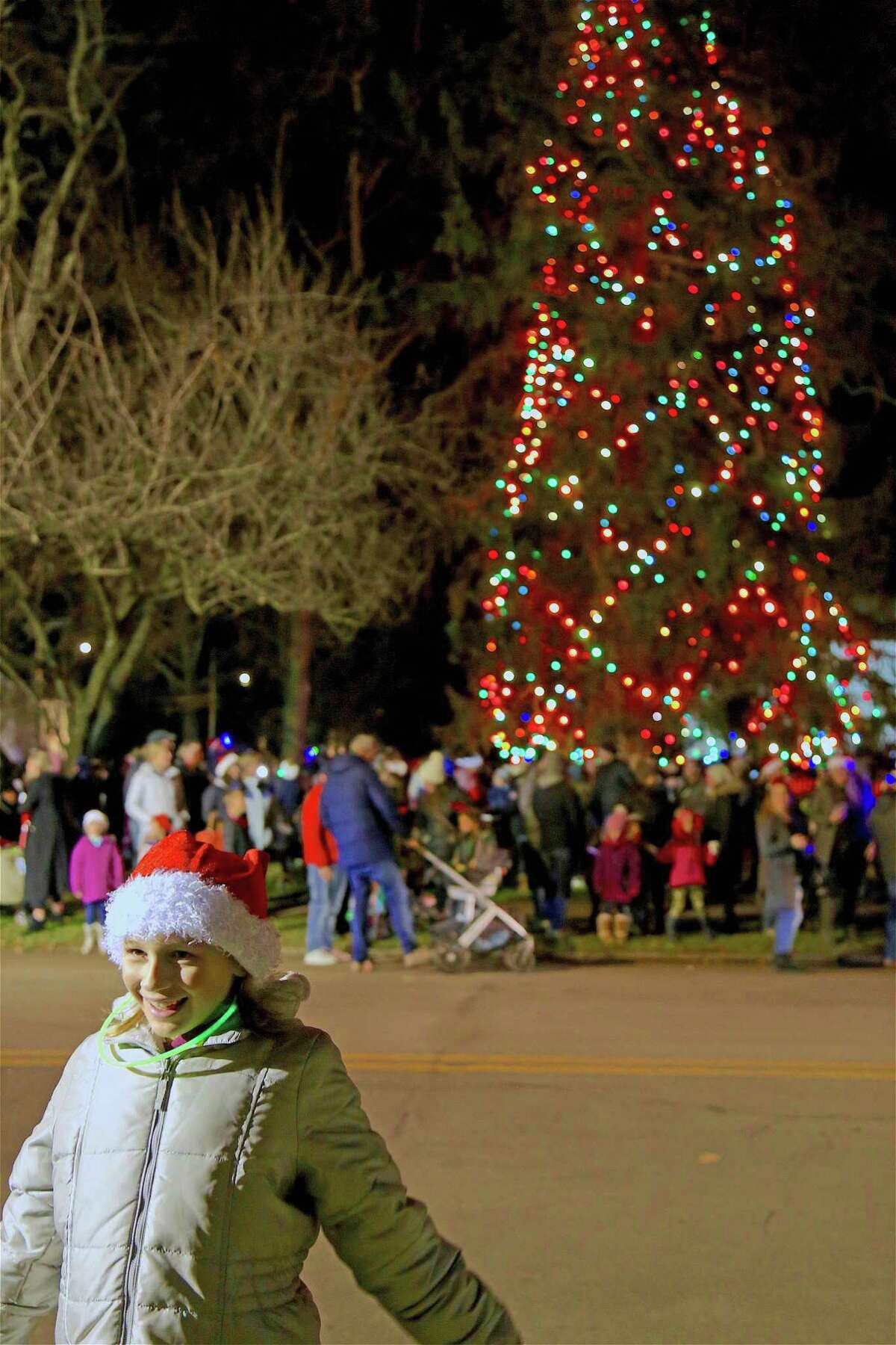 Charlotte Rotelli, 11, of Fairfield, poses for a picture just after the lights went on at the annual tree lighting at Town Hall on Friday, Dec. 6, 2019, in Fairfield, Conn.