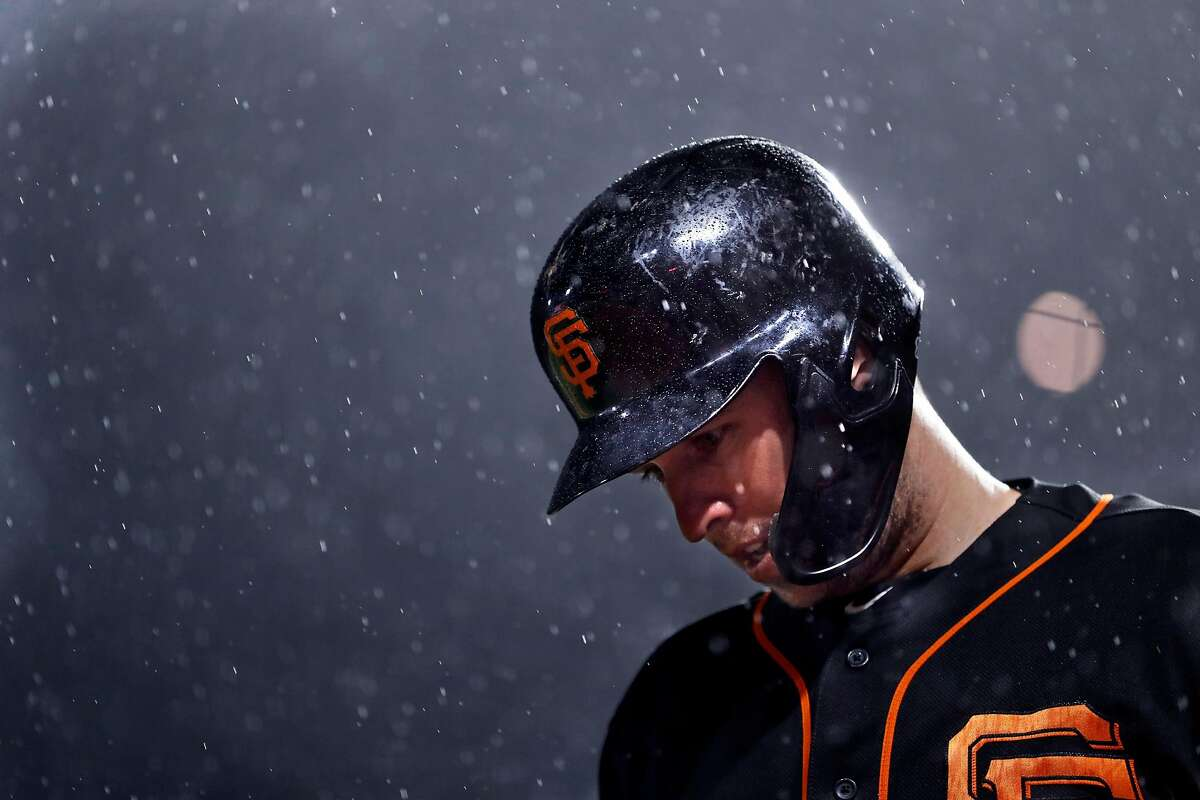 San Francisco Giants' Buster Posey waits to bat as rain falls during Bay Bridge Series game against Oakland Athletics at Oracle Park in San Francisco, Calif., on Monday, March 25, 2019.