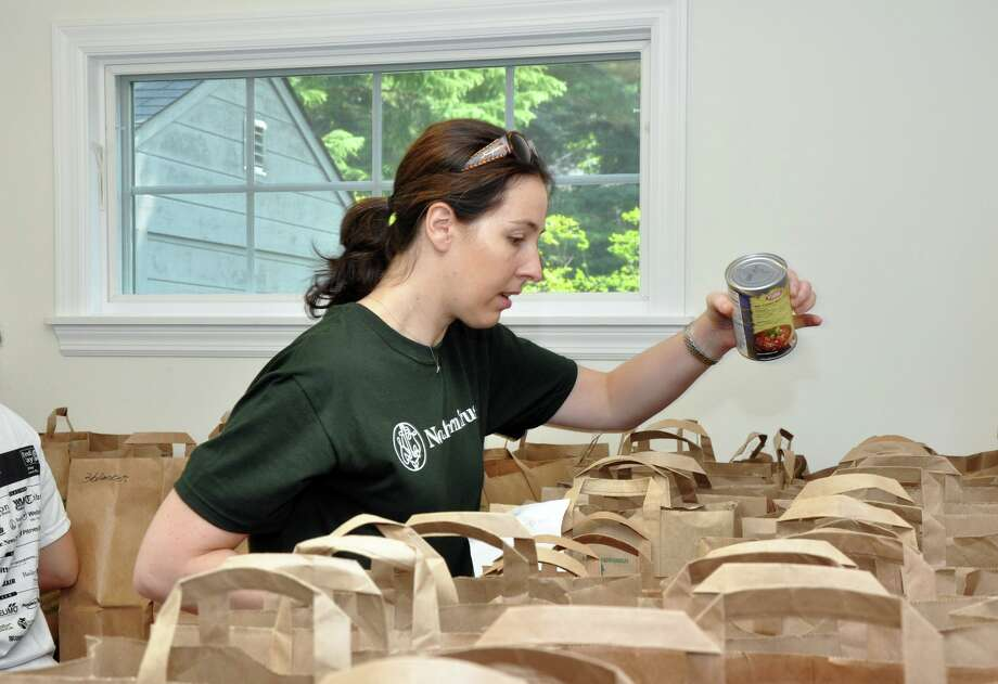 A United Way volunteer adds a can of beans to a grocery bag at the Person-to-Person pantry. Photo: File / Hearst Connecticut Media / Connecticut Post Freelance