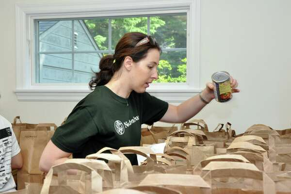 A volunteer adds a can of beans to a grocery bag at the Person-to-Person food pantry, which supplies meals to residents in need.