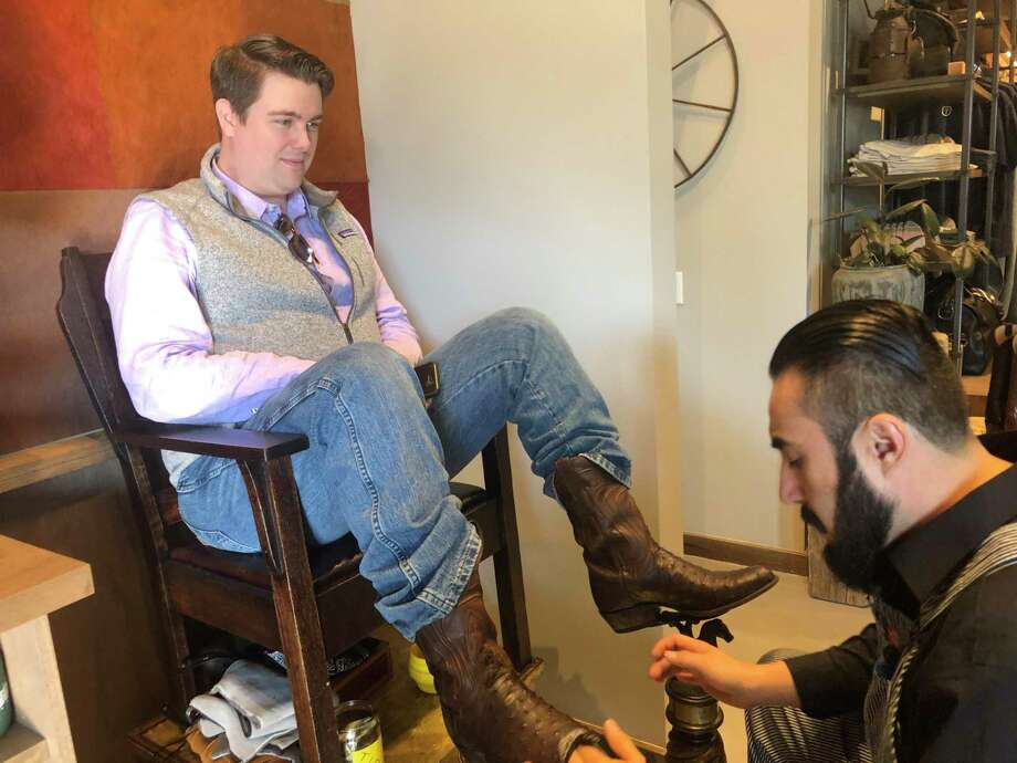 Boot Shiner Saul Amador talks with customer Chris Kannady as he works at the Tecovas grand opening in Rice Village on Saturday, Dec. 7. The Austin-based western retailer sells handcrafted boots and other leather goods. Photo: Tracy Maness / Staff Photo
