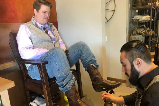 Boot Shiner Saul Amador talks with customer Chris Kannady as he works at the Tecovas grand opening in Rice Village on Saturday, Dec. 7. The Austin-based western retailer sells handcrafted boots and other leather goods.