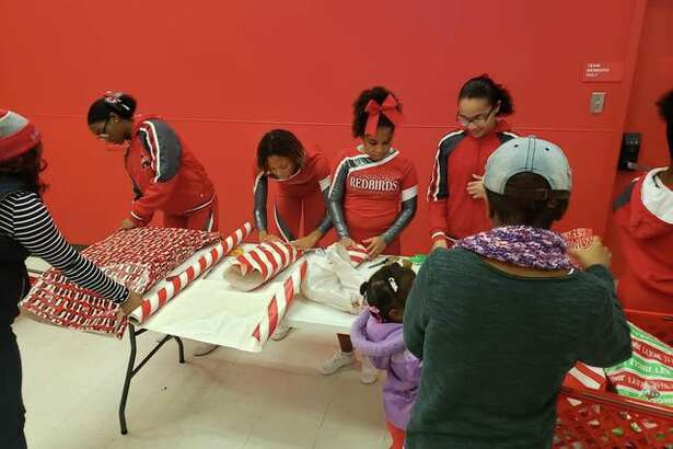 Alton School District students wrap gifts Saturday during the annual Shop With A Cop, organized by the Police Benevolent and Protective Association Alton Unit 14, at Target. The union organization supports officers of the Alton Police Department.