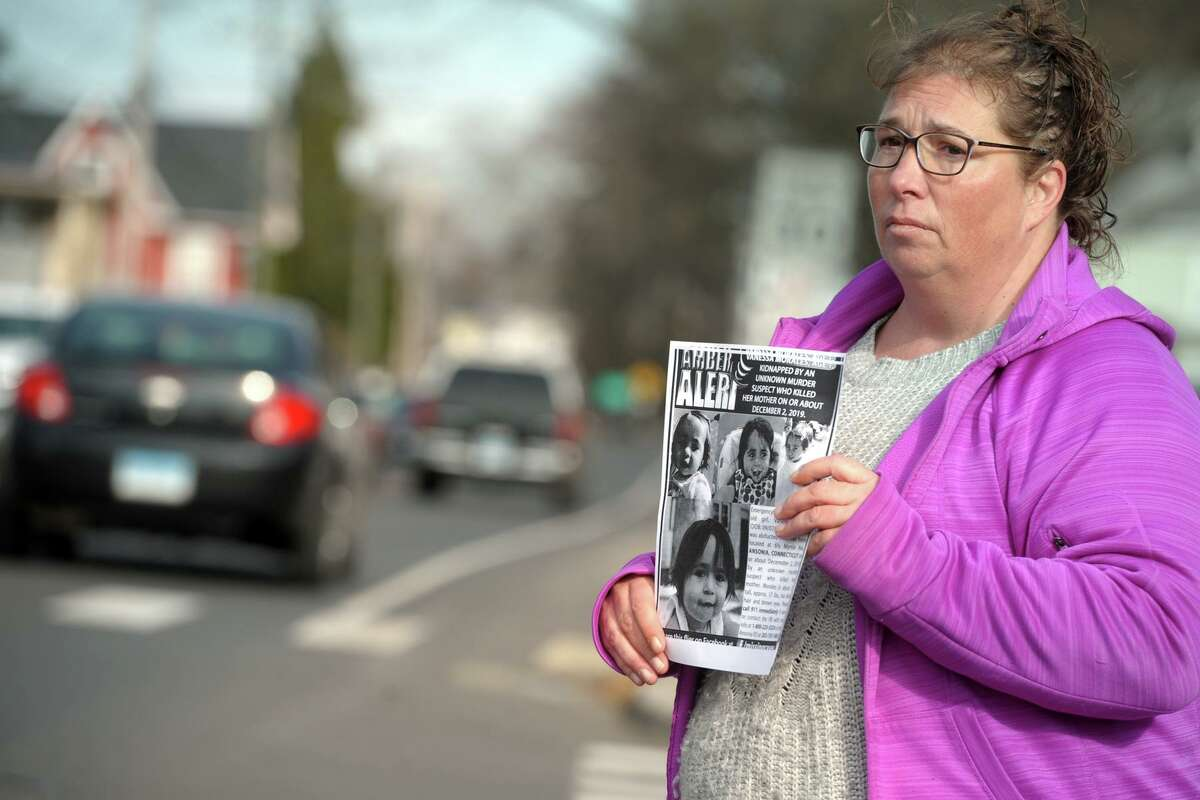 Roberta Tripp passes out fliers to passing drivers along Derby Ave. in Derby on Friday. Tripp and other volunteers were out to remind area residents to be on the lookout for 1-year-old Vanessa Morales, who has been missing since her mother, Christine Holloway, was found beaten to death in their Ansonia home on Monday.