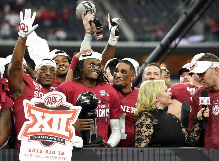 Oklahoma wide receiver CeeDee Lamb, center, holds the Most Outstanding Player award as he is congratulated by quarterback Jalen Hurts (1) after their 30-23 overtime victory over Baylor in an NCAA college football game for the Big 12 Conference championship, Saturday, Dec. 7, 2019, in Arlington, Texas. (AP Photo/Jeffrey McWhorter) Photo: Jeffrey McWhorter, Associated Press / Copyright 2018 The Associated Press. All rights reserved