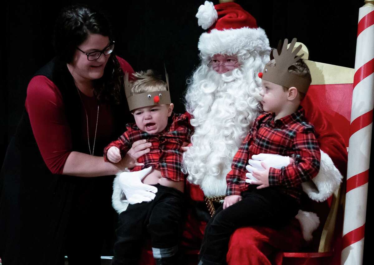 Tina Gac of Saratoga situates her younger son, Walker Gac, 2, for a photo with his older brother, Colton, 3, on Santa's lap at the Saratoga Festival of Trees in the City Center of Saratoga Springs, N.Y. on Dec. 7, 2019. (Jenn March, Special to the Times Union )