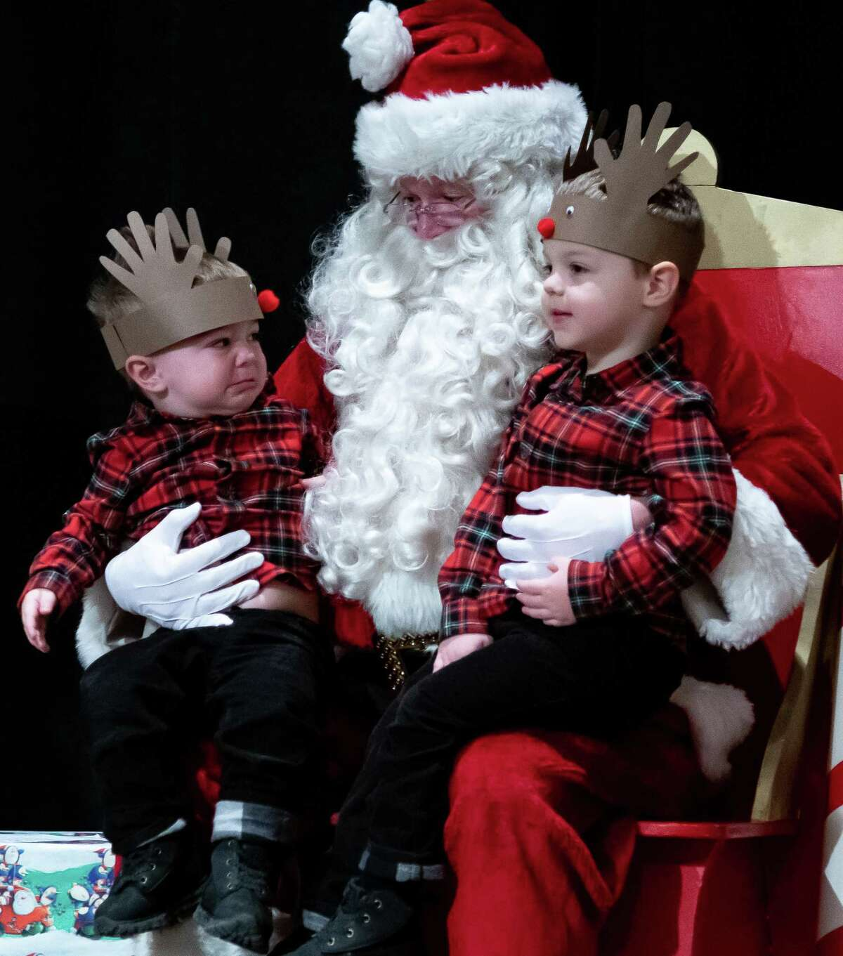 Walker Gac, 2, left, frowns at Santa after being left on his lap with his older bother, Colton, 3, by their mother for a photo at the Saratoga Festival of Trees in the City Center of Saratoga Springs, N.Y. on Dec. 7, 2019. (Jenn March, Special to the Times Union )