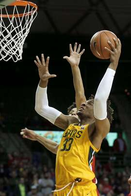 Baylor forward Freddie Gillespie (33) scores in front of Arizona guard Josh Green (0) during the second half of an NCAA college basketball game in Waco, Texas, Saturday, Dec. 7, 2019. (AP Photo/Michael Ainsworth)