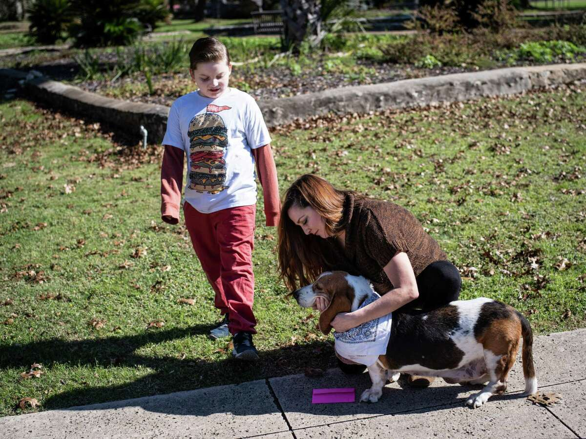 Sarah Ortiz, right, and her son Judah, left, received an envelope with free cash as they visited San Pedro Springs Park with their dog Bell, who is set to be put down tomorrow due to complications with cancer, in San Antonio, Texas on Saturday, December 7, 2019. The Awesome Foundation is an international organization with local chapters that award $1000 grants each month through an application process that promotes, ?'Awesomeness?