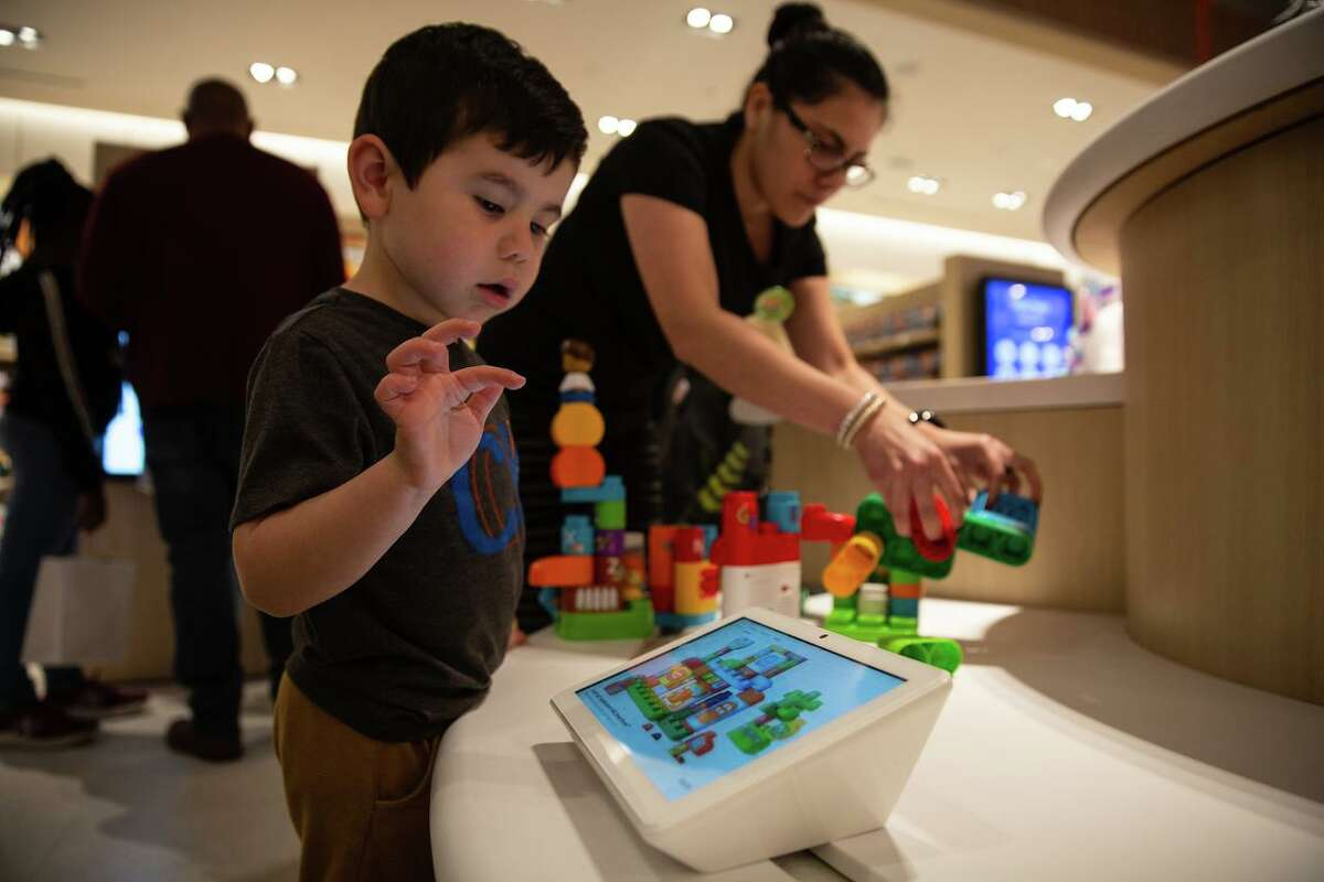 Valentin Giraldo, 4, peeks at the screen showing information about the LeapFrog toy he's playing with at Toys R Us in The Galleria.