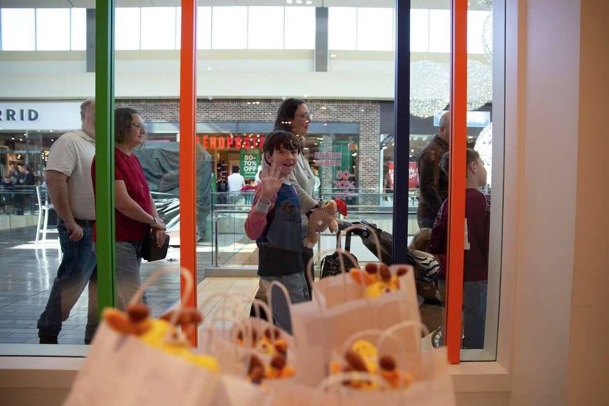 Nathan Bennett, 9, waves through the window as he makes his way through the line to get into Toys R Us in The Galleria.
