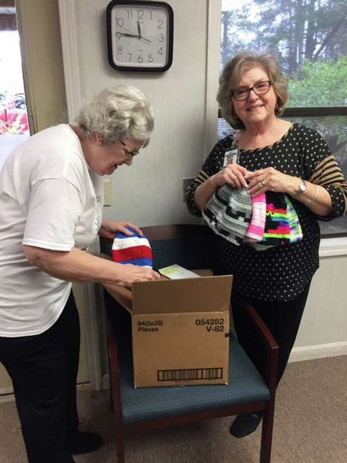Volunteers at Bridegwood Farms pour through a box of colorful hand made hats donated to Bridgewood for Christmas gifts for the residents. The hats were lovingly made by Gladys Manning of Austin, part of The RC of Conroe's extended Family of Rotary. Photo: Courtesy Photo