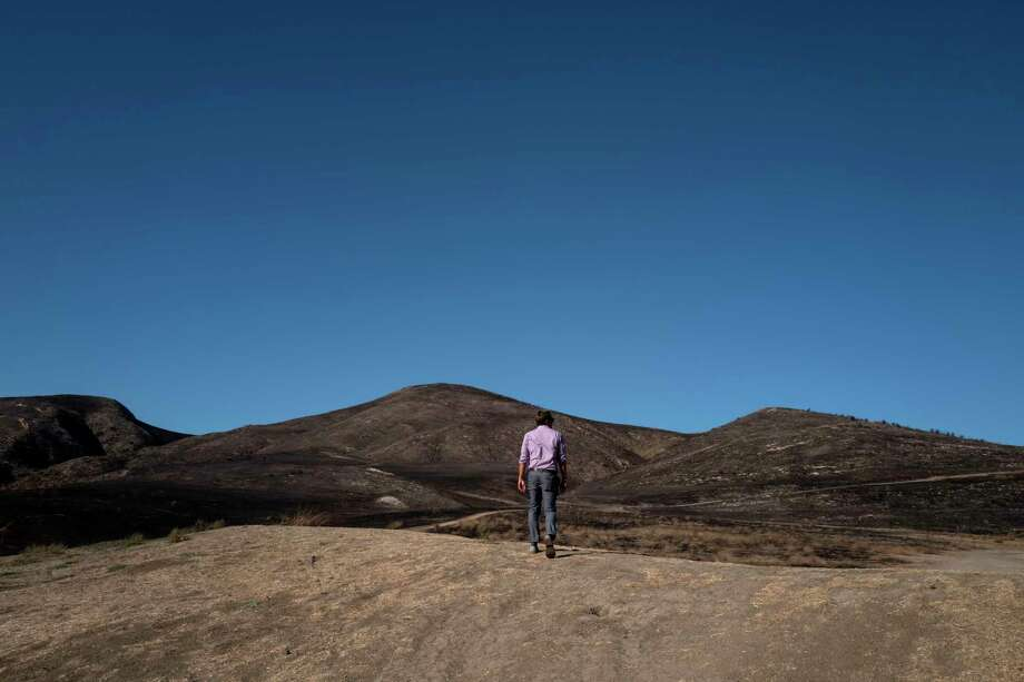A man walks across a dried and burned out landscape, a result of the Real Fire, in Goleta, Calif. The Real Fire scorched more than 400 acres in mid-October but was quickly contained due to heightened awareness and readiness by local fire departments. Photo: Washington Post Photo By Michael Robinson Chavez / The Washington Post