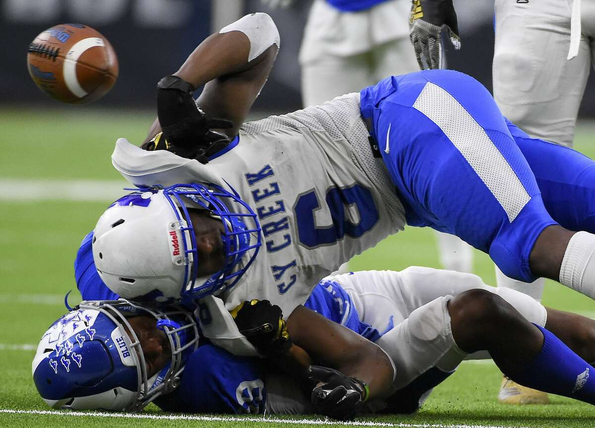 Cy Creek running back Eddie Jimwrson (6) fumbles while being tackled by Katy Taylor defensive back Hollis Robinson during the second half of a 6A division II regional final high school football game, Dec. 7, 2019, in Houston.