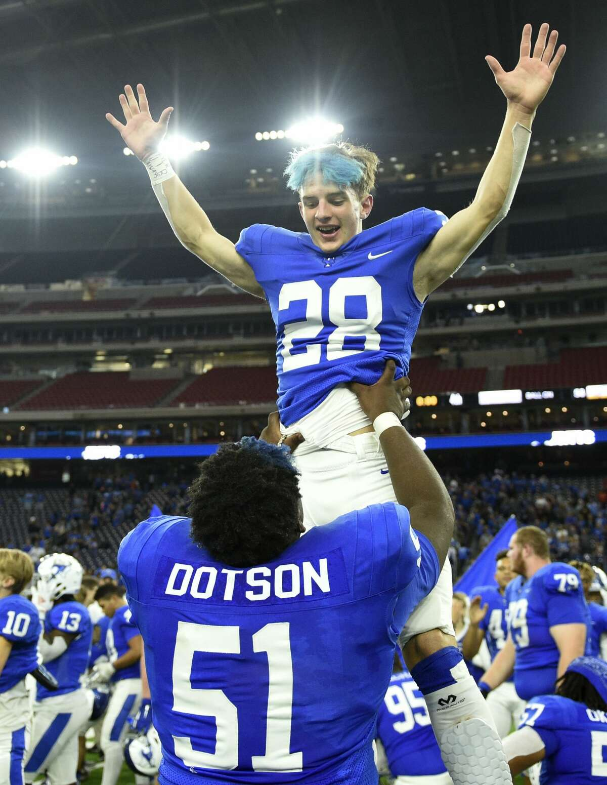 Katy Taylor's Camron Hennon (28) celebrates the team's win over Cy Creek with De'Ondre Dotson after a 6A division II regional final high school football game, Dec. 7, 2019, in Houston.