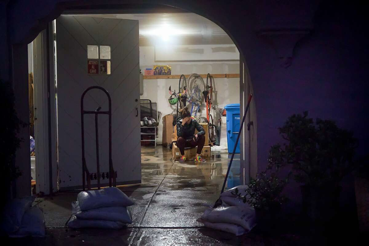 Catherine Abad sits in her flooded home during cleanup on 15th St. and Wawona St. on Saturday, Dec. 7, 2019, in San Francisco, Calif.