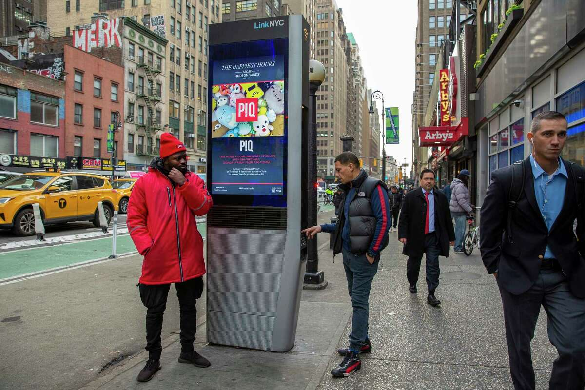 Alhassan Mohammed, left, a former professional soccer player, who uses the free Wi-Fi at LinkNYC kiosks to call his family in Ghana, in New York, on Nov. 21, 2019. LinkNYC was supposed to digitally unite the city, but the neighborhoods that need it the most have been left out. (Sarah Stacke/The New York Times)