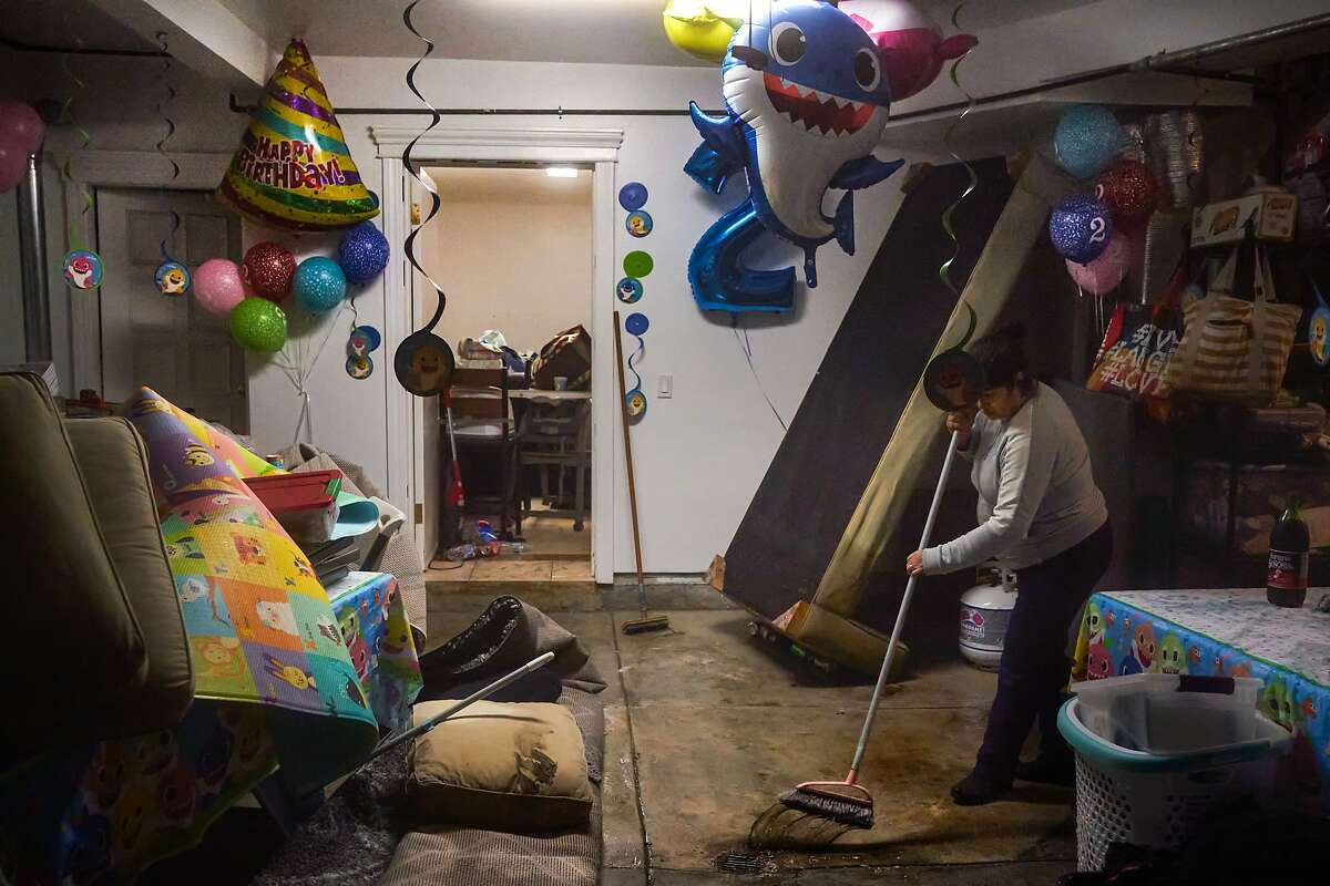 Elizabeth Flores sweeps water after her 2-year old nephew�s birthday party was interrupted by the flood at15th St. and Wawona St. on Saturday, Dec. 7, 2019, in San Francisco, Calif.