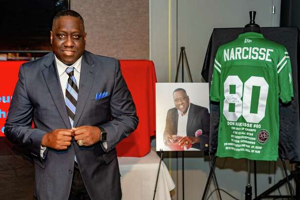 Former Lincoln High School graduate and CFL WR Don Narcisse stands with his official photo and his old jersey as he is inducted into the Museum of the Gulf Coast in Port Arthur on Saturday. Fran Ruchalski/The Enterprise