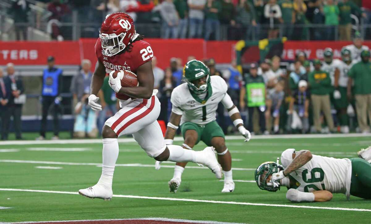 ARLINGTON, TX - DECEMBER 07: Rhamondre Stevenson #29 of the Oklahoma Sooners runs the ball across the goal line to score the winning touchdown in overtime of the Big 12 Football Championship as Grayland Arnold #1 and Terrel Bernard #26 of the Baylor Bears look on at AT&T Stadium on December 7, 2019 in Arlington, Texas. Oklahoma won 30-23. (Photo by Ron Jenkins/Getty Images)