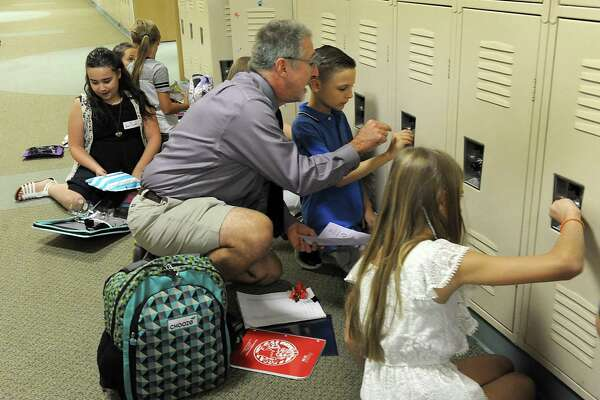 Richard Need, a math, science and homeroom teacher at Reed Intermediate School in Newtown, helps Stephen Vereshagin figure out his locker combination, Monday, August 28, 2017. Monday was the first day of school for Newtown kids.