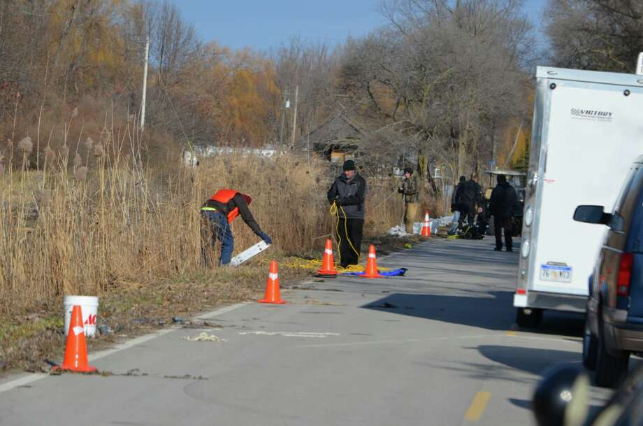 Police search the ditch on Thomas Road Saturday after a vehicle was found submerged Friday afternoon. The driver of the vehicle has not yet been located. Photo: (Tuscola County Sheriff's Office)