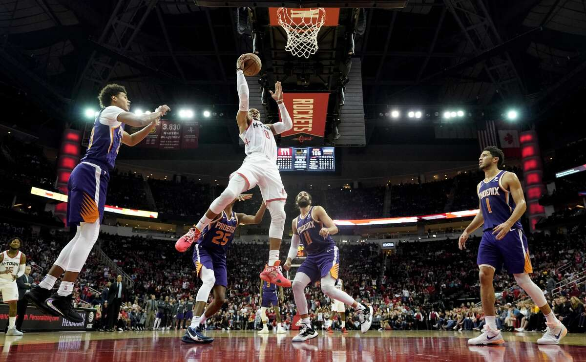 Houston Rockets' Russell Westbrook (0) goes up for a shot as Phoenix Suns' Devin Booker (1), Ricky Rubio (11), Mikal Bridges (25) and Cameron Johnson defend during the second half of an NBA basketball game Saturday, Dec. 7, 2019, in Houston. The Rockets won 115-109. (AP Photo/David J. Phillip)