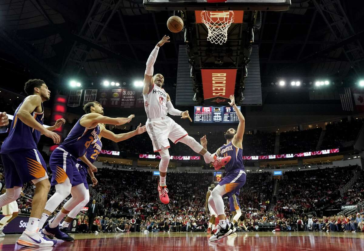 Houston Rockets' Russell Westbrook (0) goes up for a shot as Phoenix Suns' Ricky Rubio (11), Cameron Johnson (23) Dario Saric,, second from left, and Devin Booker (1) defend during the second half of an NBA basketball game Saturday, Dec. 7, 2019, in Houston. The Rockets won 115-109. (AP Photo/David J. Phillip)