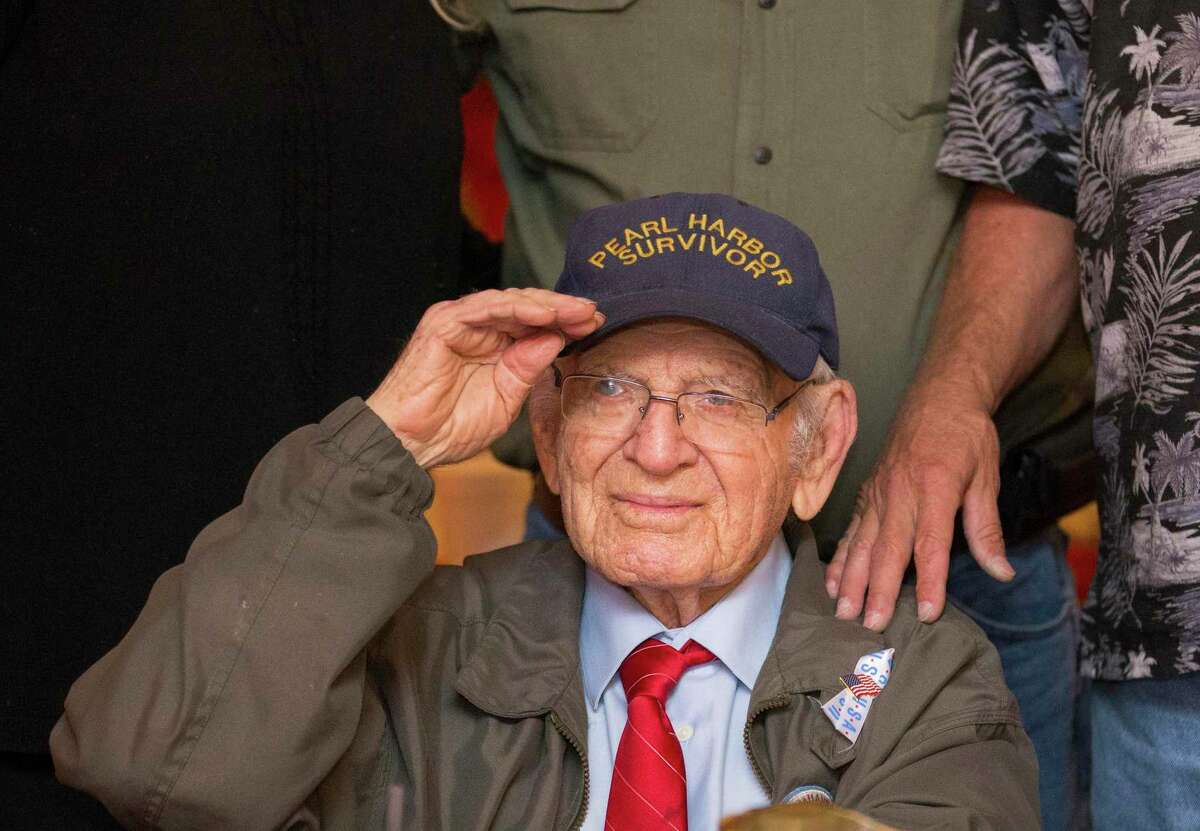 Pearl Harbor survivor William St. John, 98, salutes while having his photo taken after a Pearl Harbor Day remembrance luncheon at the Little Red Barn restaurant.