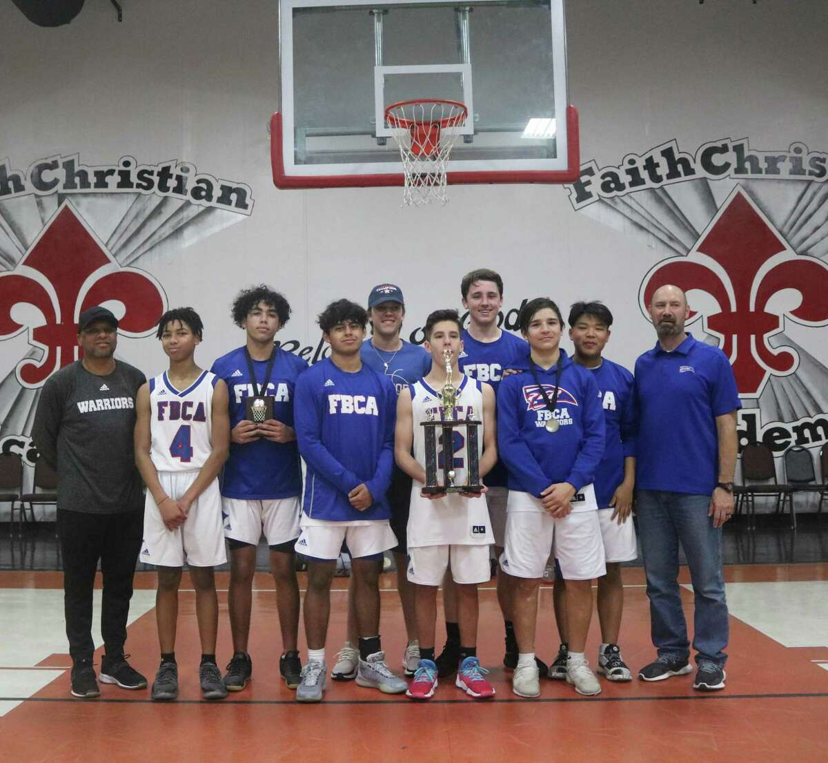 Pasadena-FBCA's varsity boys basketball team poses with their first tournament championship trophy in many years Saturday night.  The Warriors averaged 71.6 points in downing three opponents.