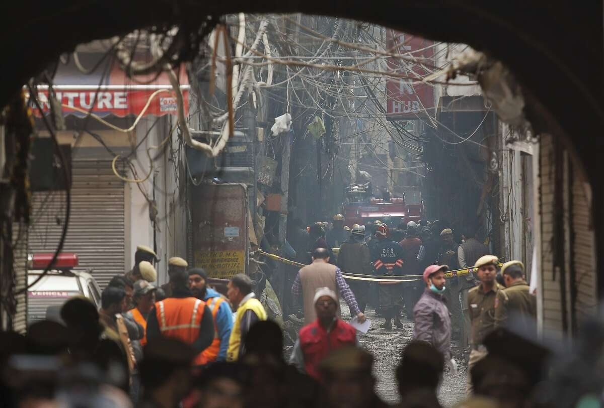 A fire engine team works in an alley near the site of the factory fire in the Karol Bagh district of New Delhi. Building laws and safety norms are routinely flouted in the highly congested area.