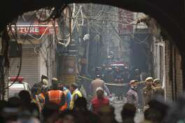 A fire engine stands by the site of a fire in an alleyway, tangled in electrical wire and too narrow for vehicles to access, in New Delhi, India, Sunday, Dec. 8, 2019. Dozens of people died on Sunday in a devastating fire at a building in a crowded grains market area in central New Delhi, police said. (AP Photo/Manish Swarup)
