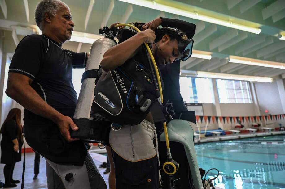 Dive master Kim Walker helps Abreya Rubia, 16, a junior at Dunbar High School in Washington, D.C., with her equipment before her first time scuba diving. Photo: Washington Post Photo By Michael Robinson Chavez / The Washington Post