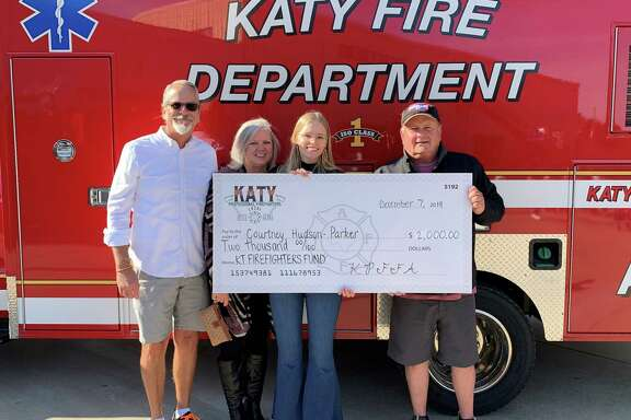 Courtney Hudson-Parker received a $2,000 scholarship from theKaty Professional Fire Fighters Association at its second annual Pancakes with Santa breakfast. With Courtney are her parents andStephen Jahn, director of legal operations at Veterans MFG LLC. The company is one of the association's corporate sponsors, the other being H-E-B as well as a number of Secret Santas.