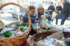 """Hazel McCauley, 8, and her sister Violet McCauley, 6, sort through holiday treats they were helping pass out to shoppers passing by the Greenwich Baptist Church """"A Taste of Christmas"""" booth during the 11th Annual Holiday Stroll in Greenwich, Conn. on Dec. 7, 2019."""